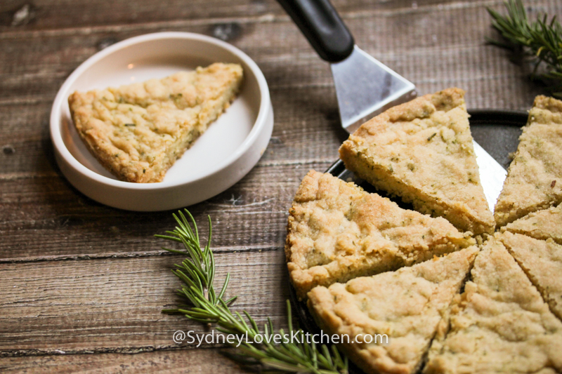rosemary shortbread slice on a white plate and the whole pie of slices next to it and a couple of sprigs of rosemary on the side.