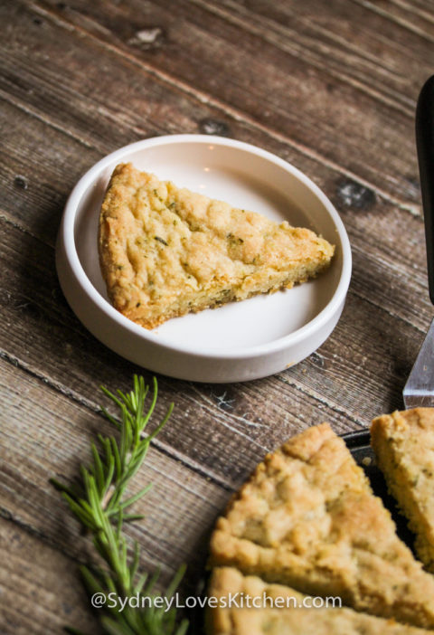 rosemary shortbread cookie slice on a white plate with a rosemary sprig in the foreground
