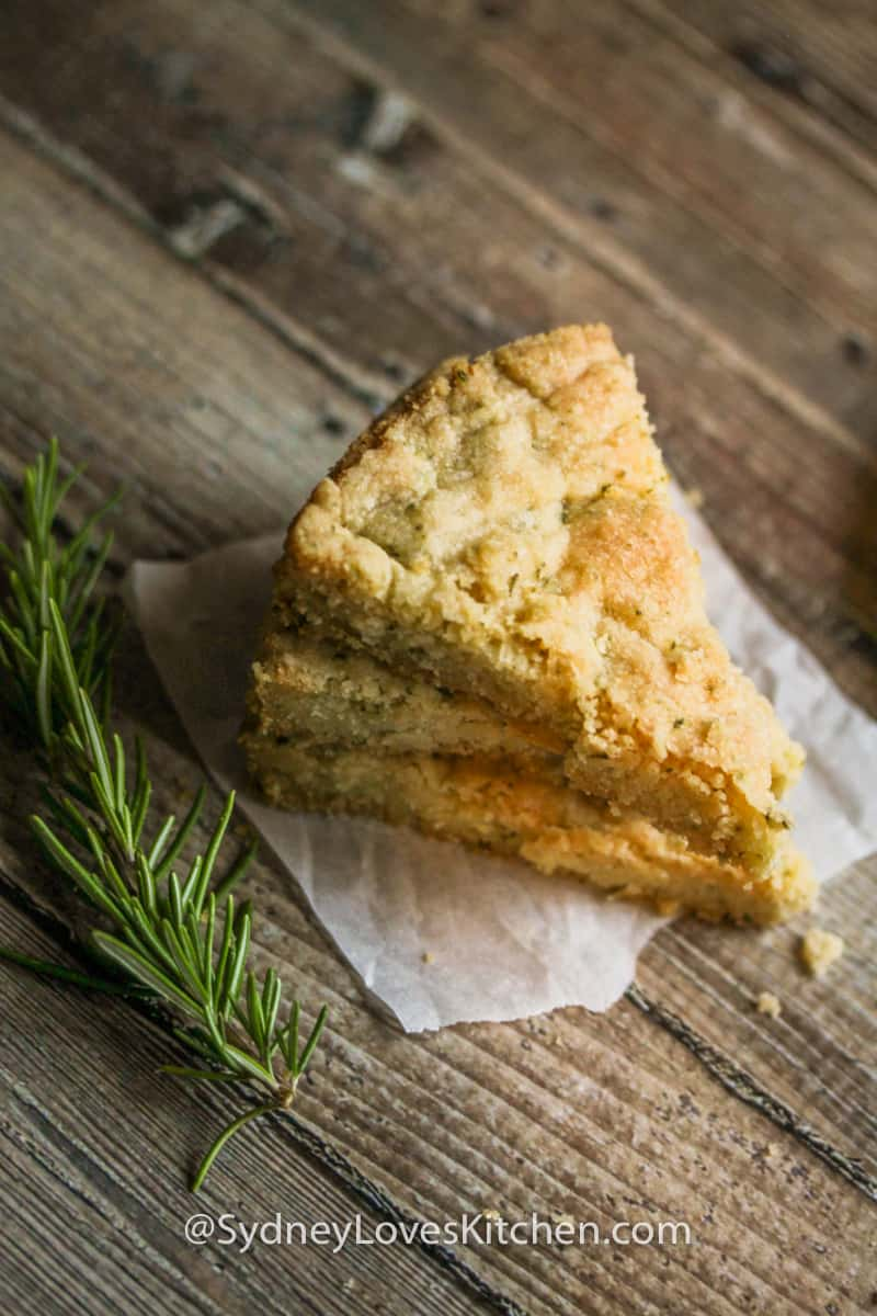 three slices of rosemary shortbread cookies stacked on top of each other with a sprig of rosemary in the foreground