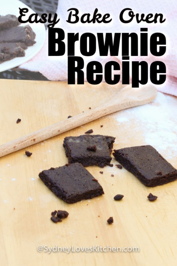 Easy Bake Oven Brownie Recipe with 3 brownies, a wooden spoon and some flour on the board, with a plate of brownies and a pink towel in the background