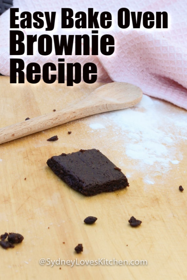 Easy Bake Oven Brownie with flour on the board, a wooden spoon and a pink towel in the background