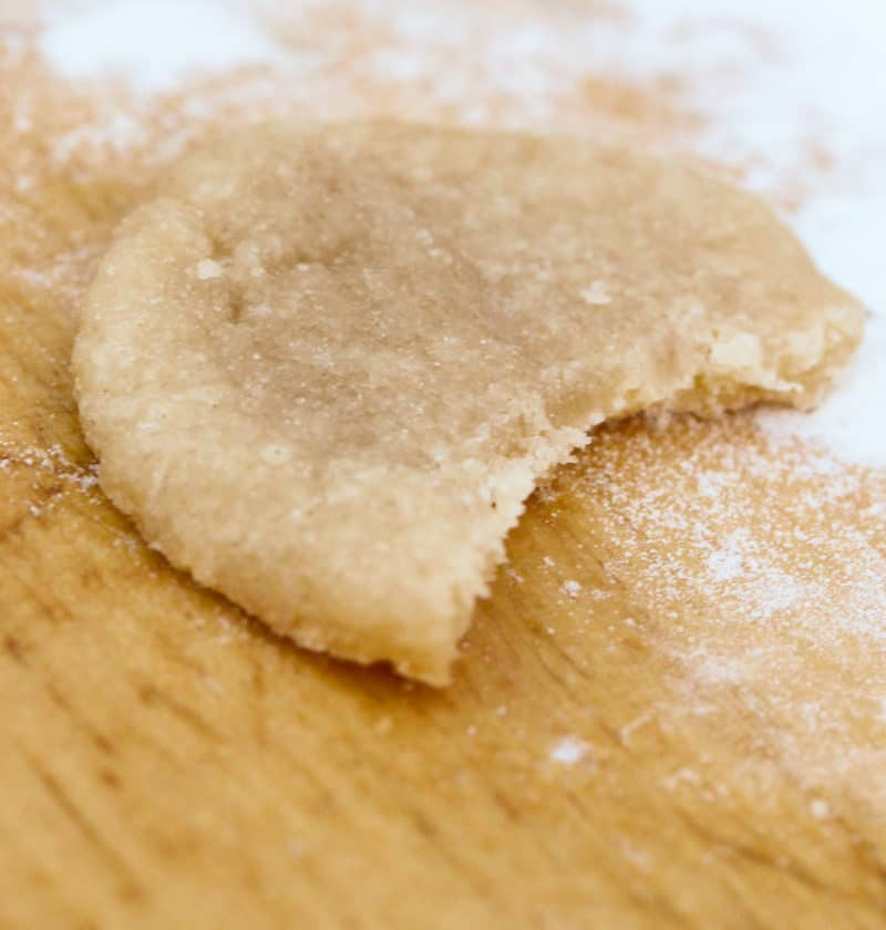 close up of an Easy Bake Oven Sugar Cookie with a bite out of it on a wood board