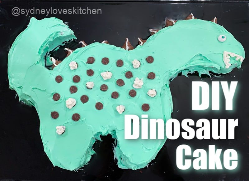 DIY dinosaur cake with green frosting, chocolate chips, and Hersey's Kisses