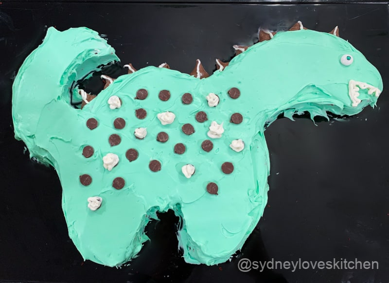 Green decorated dinosaur cake with chocolate chips and Hersey's Kisses.