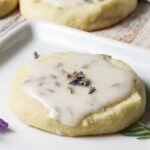 Lavender cookie with lemon frosting on a white plate.